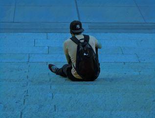 man sitting on steps blue hue backpack backside view