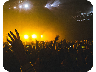 crowded people at a concert image with yellow lights
